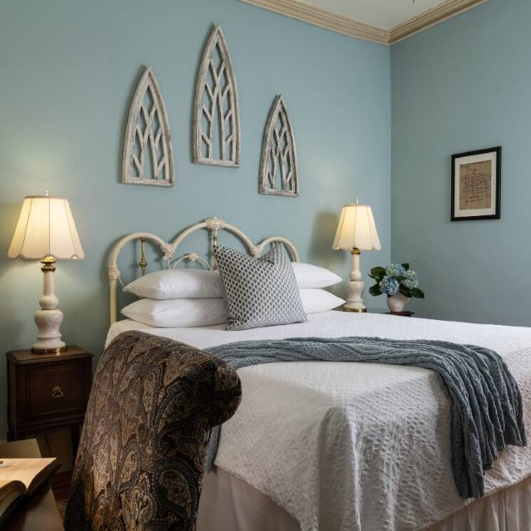 Elegant guest room with queen bed, iron headboard and side tables with white lamps