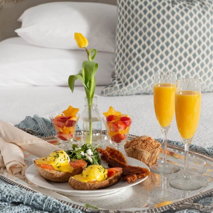 Silver tray on a bed holding a gourmet breakfast plate, flutes of orange juice and a flower