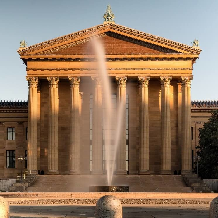 front facade of a white stone museum with columns and tall fountain
