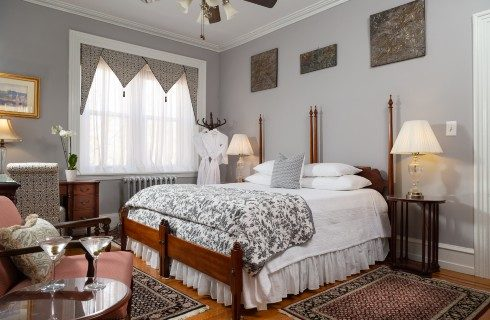 Spacious guest room with king bed, large window and sitting chair with table