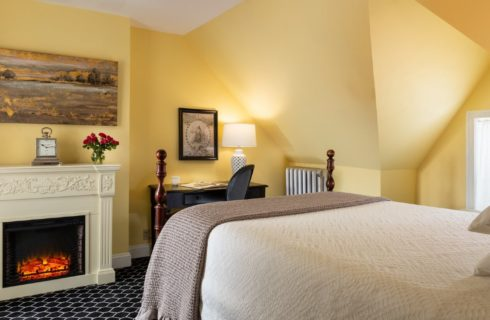 Cozy guest suite with fireplace, sitting table and yellow walls