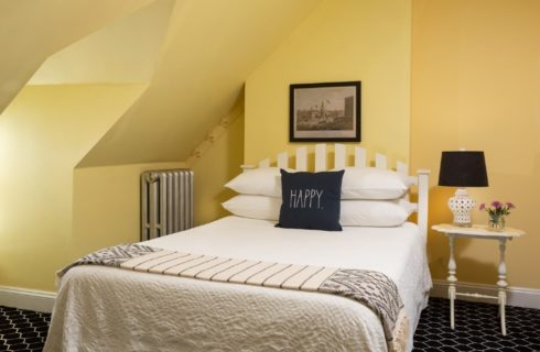 Cozy bedroom with bed, side table and lamp, and yellow angled walls