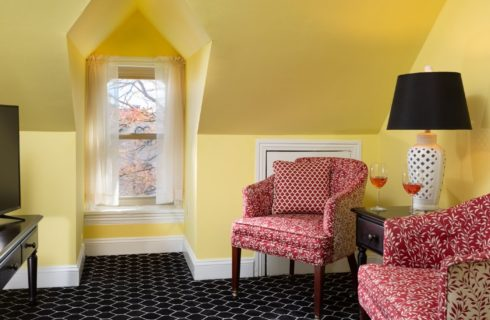 Sitting area with yellow walls, inset window, and red upholstered sitting chairs by a TV