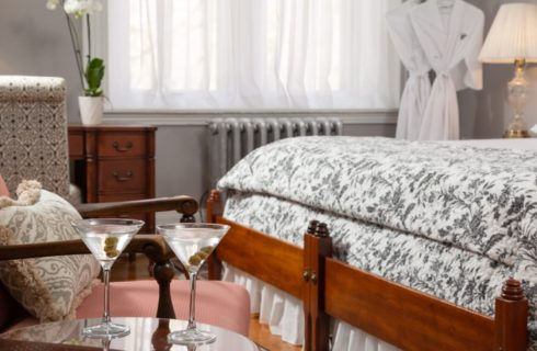 Salmon colored sitting chair by a table holding two martinis in a bedroom with king bed and hanging robes