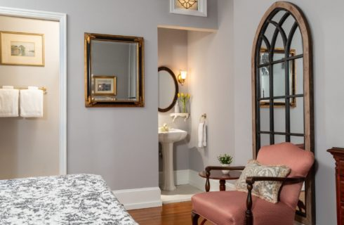 Guest room with bed, sitting chair and pedestal sink with mirror in corner cove
