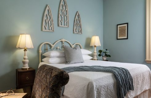 Guest room with white bed, side tables with lamps, desk and chair and blue walls