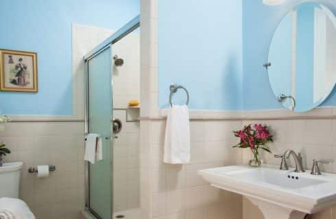 Bathroom with toilet, stand up shower and white pedestal sink under a large round mirror
