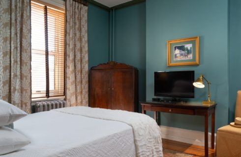 Bedroom with queen bed, brown armoire and desk with TV and lamp