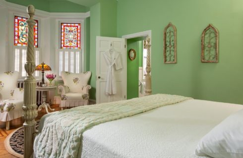 Large bedroom with four poster bed, sitting area with chairs by large, colorful stained glass windows