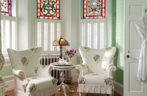 Two flowered wingback chairs under beautiful stained glass windows near open door with a hanging robe