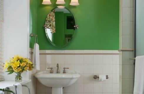 One white pedestal sink under an oval mirror in bathroom with white tile and green walls