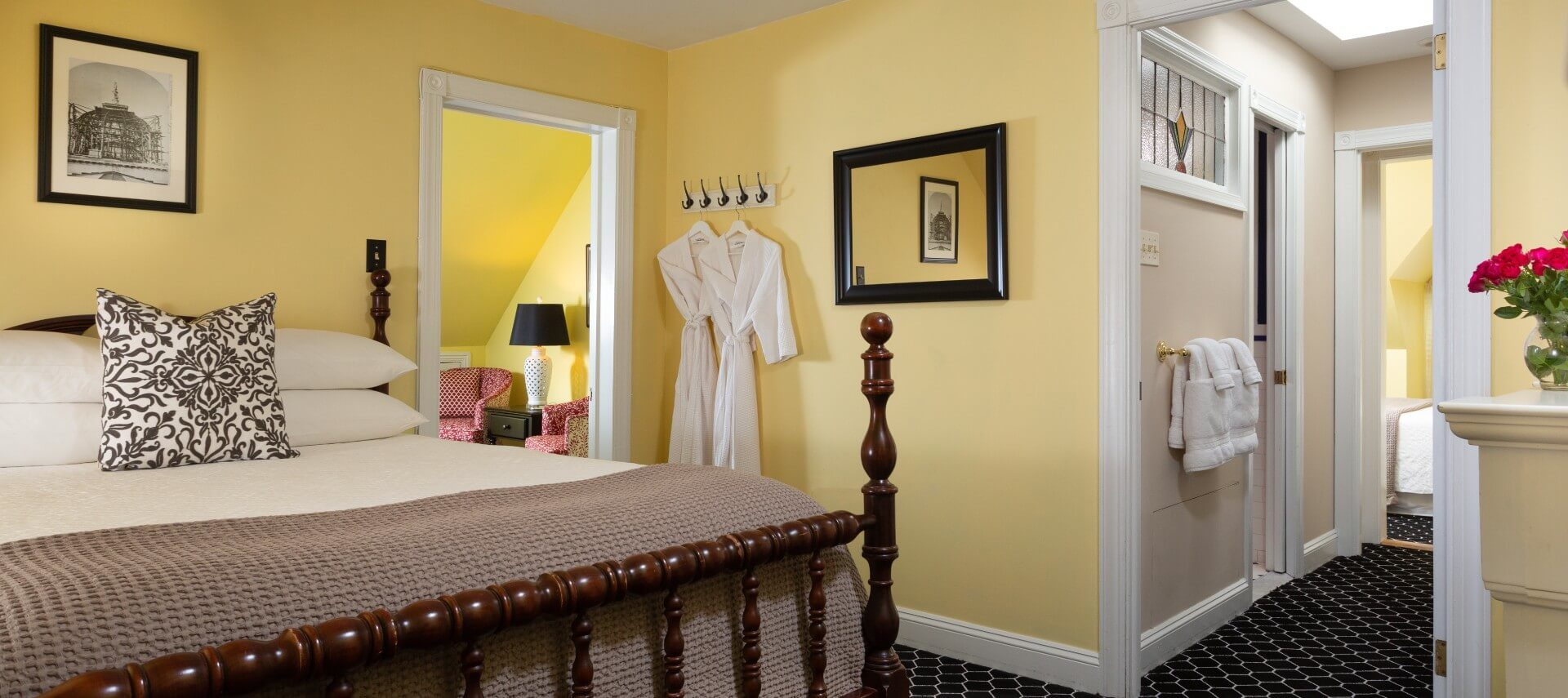 A large guest suite with queen bed, separate sitting room and hallway to an ensuite bathroom