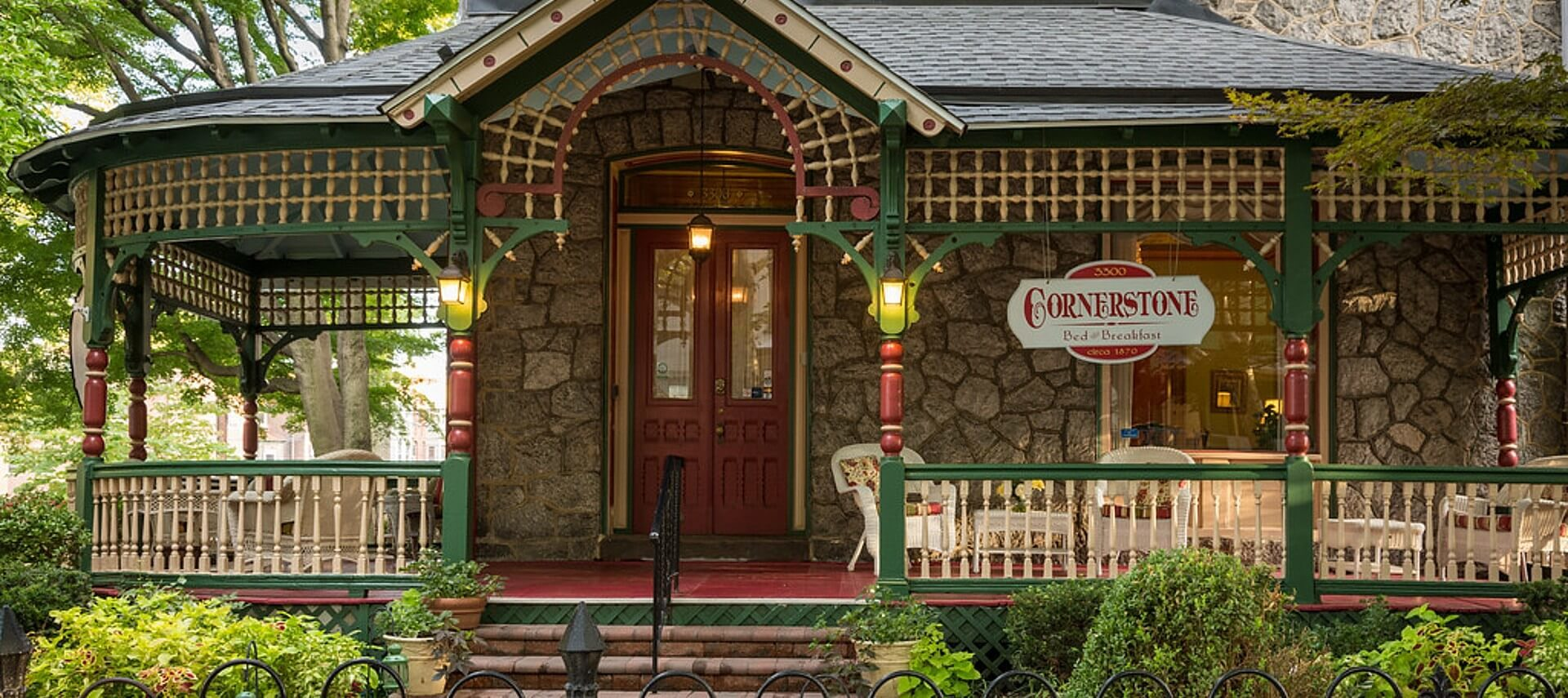 Front facade of a home with stone walls and large wrap around porch painted green and red