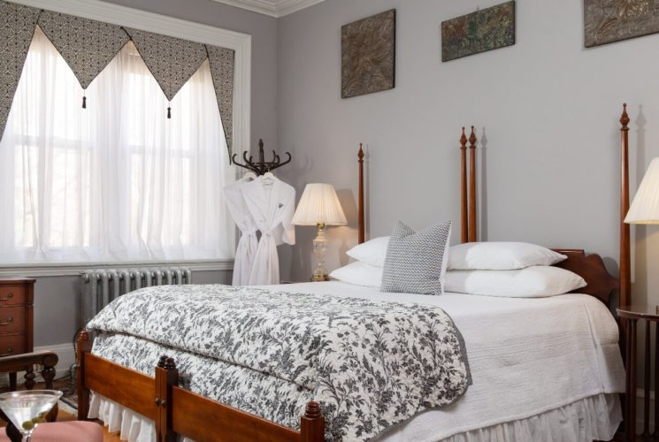 Spacious guest suite with king bed, side tables with lamps and sitting chair with a table