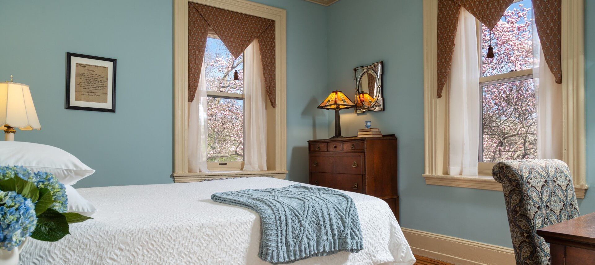 Guest room with white bed, two large windows, dresser and sitting desk with chair