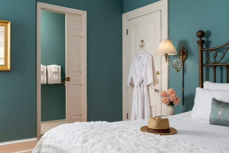 Bedroom featuring queen bed with wrought iron headboard, wall lamps and doorway into private bath