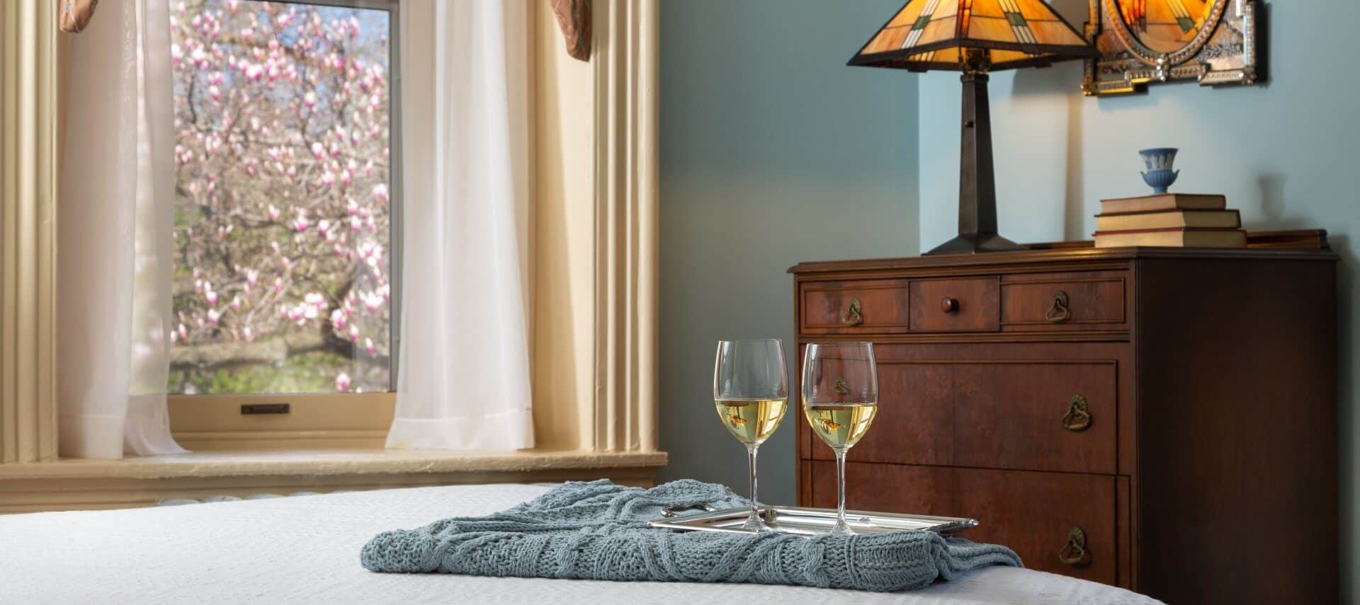 Two glasses of white wine on silver tray sitting on a bed in a room with a window and brown dresser