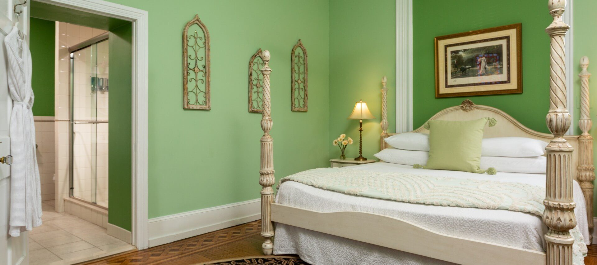 Large bedroom with four poster bed, green walls and doorway into bathroom with hanging robes
