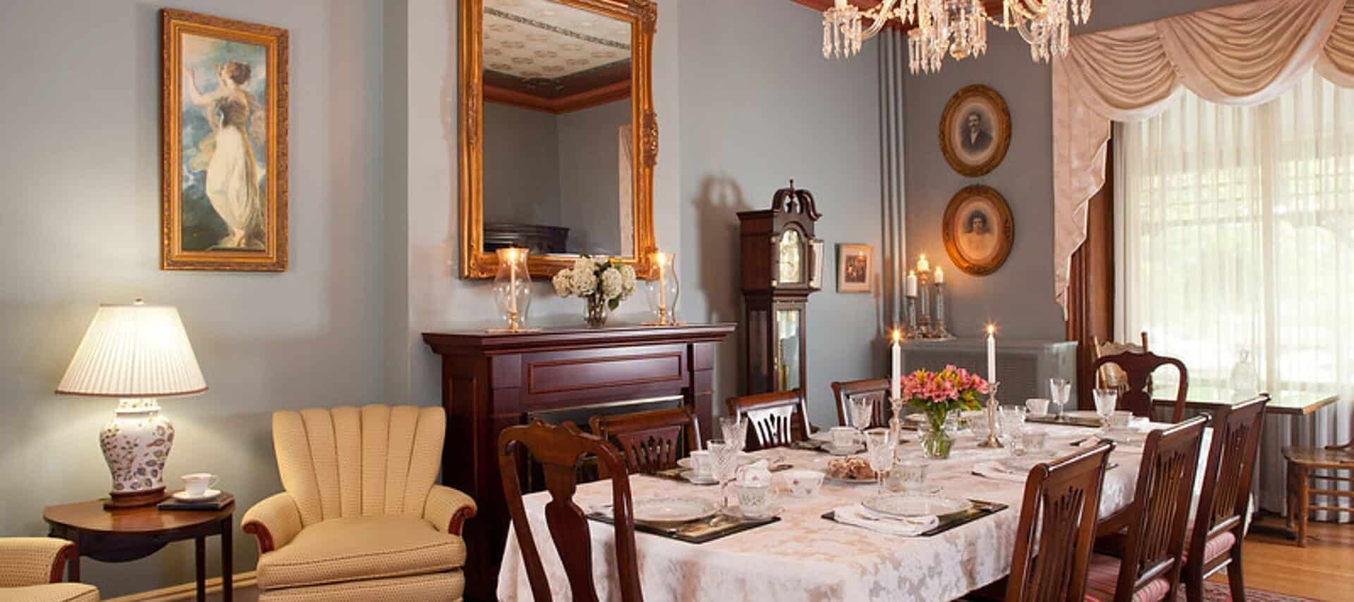 Dining room of a stately home with table set for eight, fireplace with large mirror and two sitting chairs with a table