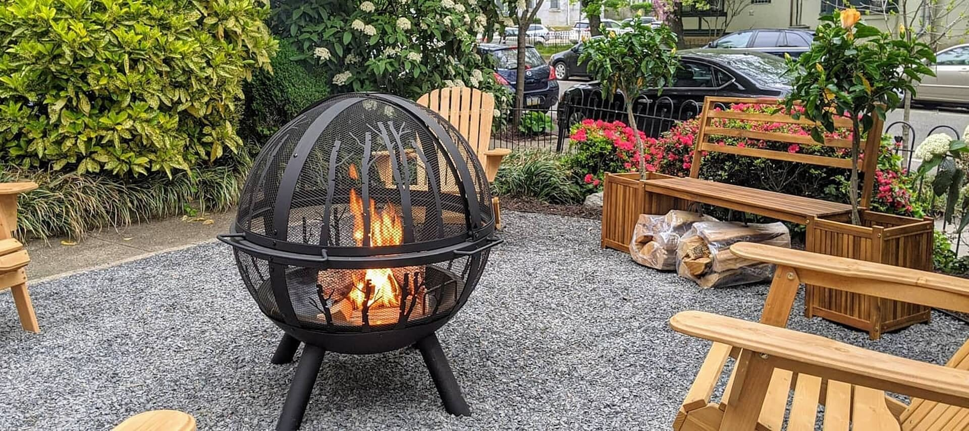 Outdoor fire pit in the shape of a globe surrounded by wooden adirondack chairs