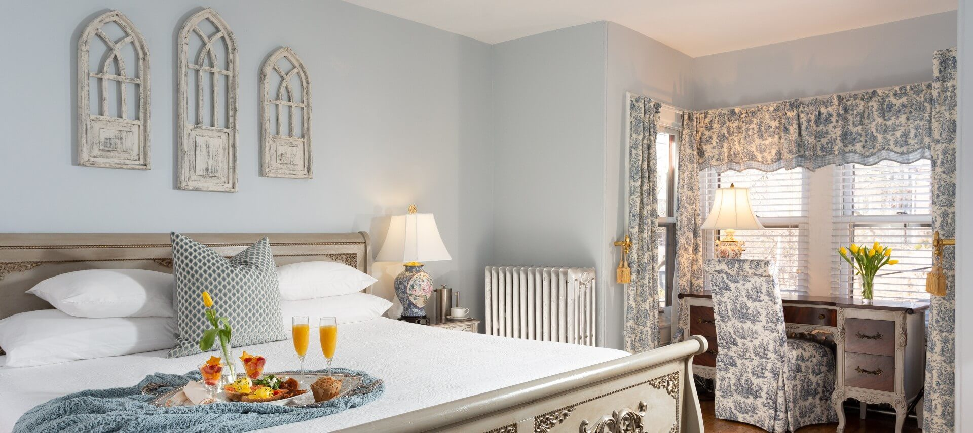 Elegant guest suite with king bed and sitting chair and table in nook with windows