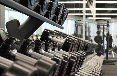 A rack of dumbells in a gym by a wall of mirrors