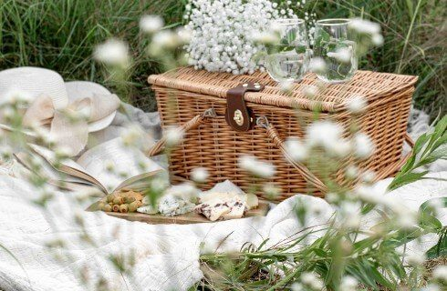 A brown picnic basket with a wooden plate of snacks on a white blanket in the grass