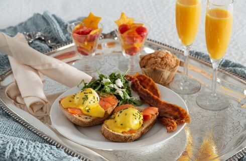 Silver platter holding a plate of breakfast, a muffin and two flutes of orange juice