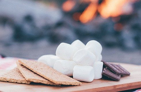 A wooden platter holding graham crackers, marshmallows and pieces of chocolate