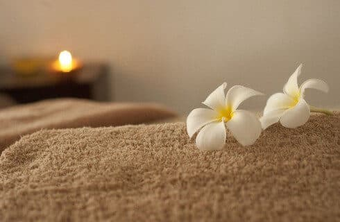 A brown towel with two white and yellow flowers an a candle lit in the background